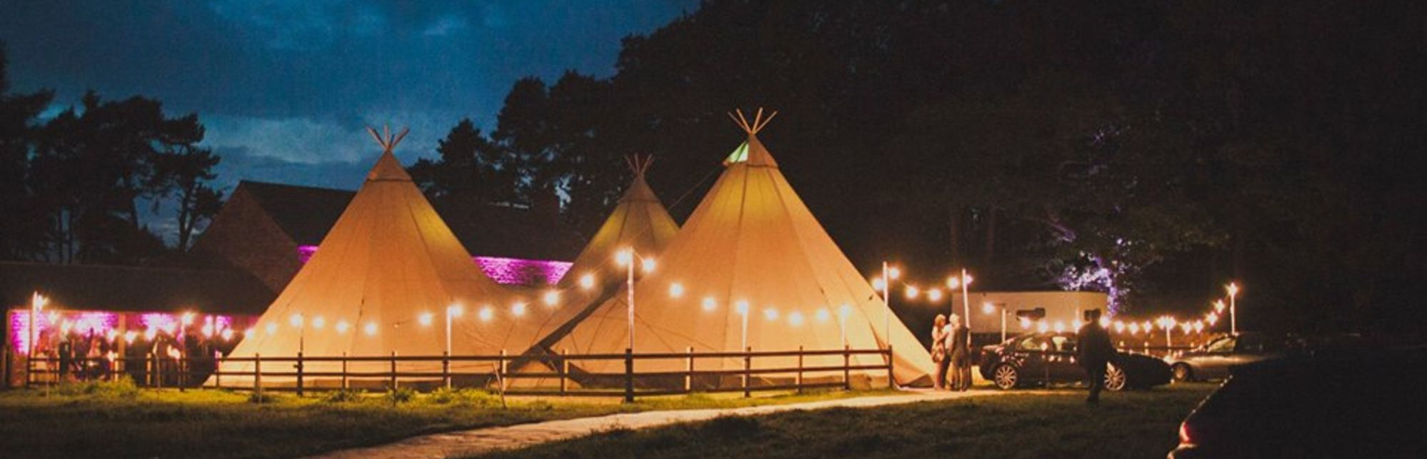 Tipis with lights outside at night
